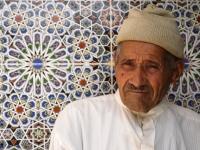 Un marocain assit devant la mosquée